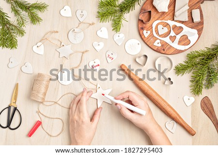 Creating hand made christmas ornaments and tags with modeling clay. DIY personalized xmas decoration. Flat lay, top view Royalty-Free Stock Photo #1827295403