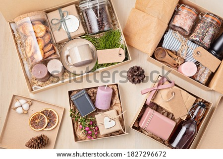 Preparing care package, seasonal gift box with coffee, cookies, spices and cups. Personalized eco friendly basket for family and friends for thankgiving, christmas, mothers and fathers day holidays Royalty-Free Stock Photo #1827296672