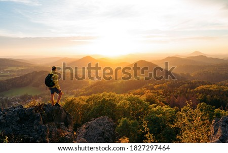 A hiker walking on a mountain meadow in spring or autumn. Hiking in the Lusatian mountains. Hiker, Backpacking on top of a mountain cliff landscape and trekking in it. Concept: Adventure, Art, Travel #1827297464