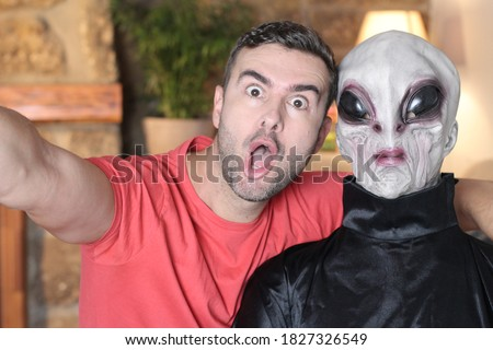 Surprised man taking a selfie with an alien   Royalty-Free Stock Photo #1827326549