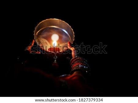 Young Indian woman celebrating Karva Chauth at night. Karva Chauth is a one-day festival celebrated by Hindu women four days after purnima (a full moon) in the month of Kartika.