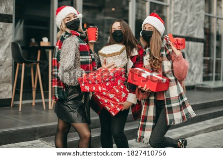 Three portrait of young happy women in red Christmas clothes, medical masks, hats and gifts walking in the city and shopping in quarantine. New year, boxes, girlfriends, shop, coronavirus, pandemic Royalty-Free Stock Photo #1827410756