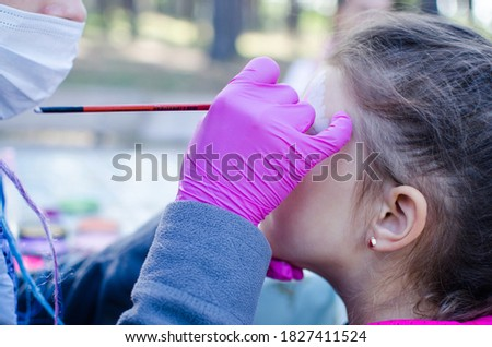 Face painting for kids party, animator, event, birthday, entertainment. The artist draws vivid drawings on the face, observing protection in quarantine conditions, with gloves and a mask.