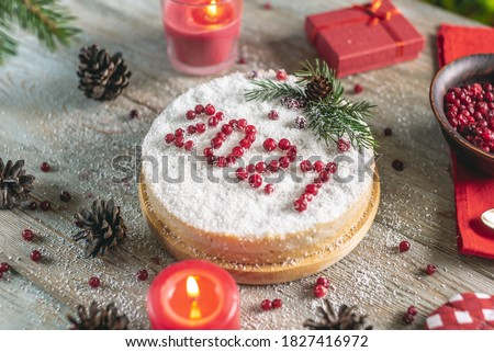 A white holiday mousse cake covered with coconut flakes, imitating snow. On the cake, the number 2021 is put out in red berries. The concept of a New year. Royalty-Free Stock Photo #1827416972