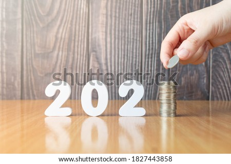 2021 New year saving money and financial planning concept. Hand putting coins on stack with 2021 number on wooden table. Creative idea for business growth, tax payment, investment and banking. #1827443858