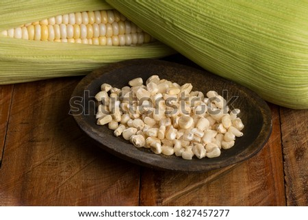 Zea mays - Wooden bowl with raw corn kernels, on wooden background. Royalty-Free Stock Photo #1827457277
