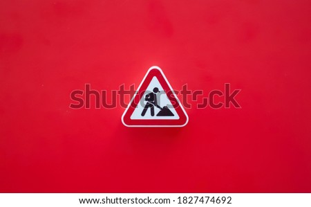 Road repair sign isolated on a red background