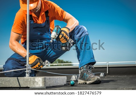 Caucasian Technician Worker Finishing Wires Installation on Building, Part of Roof of Lightning Protection System. Interception of Direct Lightning Strike.s Royalty-Free Stock Photo #1827476579