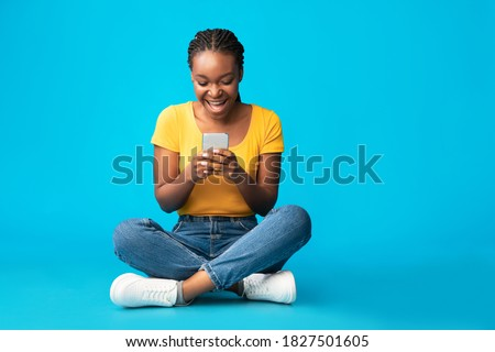 Excited Black Woman With Smartphone Using Mobile Phone Application Sitting Over Blue Studio Background. Texting, Communication, Cellphone App Concept. Free Space For Text Royalty-Free Stock Photo #1827501605