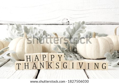Happy Thanksgiving greeting on wooden blocks against a white wood background with white pumpkins and autumn leaves #1827506030