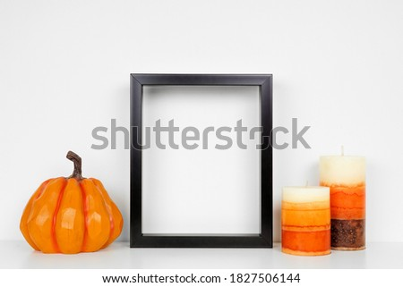 Mock up black frame with fall candles and pumpkin decor on a white shelf. Autumn concept. Portrait frame against a white wall.