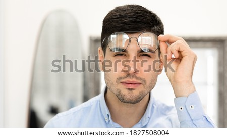 Poor Eyesight Concept. Portrait of handsome young man with spectacles squinting, trying to look closer, reading text on test chart, banner, copy space. Guy with bad vision at optics store Royalty-Free Stock Photo #1827508004