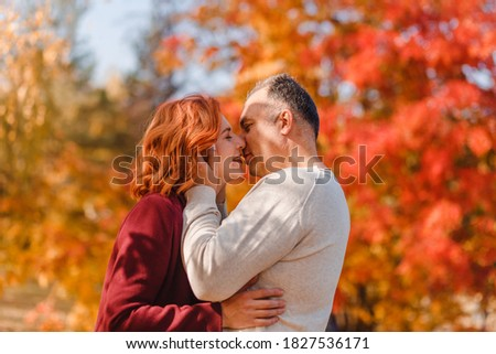 A middle-aged couple kisses in the park in the fall. autumn photo shoot