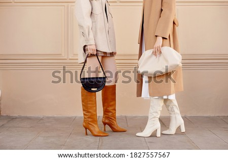 Autumn fashion two women in trendy clothes coat, high boots, bags . Street style outfit Royalty-Free Stock Photo #1827557567