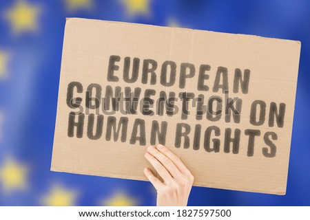 """The phrase """"European Convention on Human Rights """" on a banner in men's hand with blurred European Union flag on the background. Equality. Relationship. Conflict. Confrontation. Violence Royalty-Free Stock Photo #1827597500"""