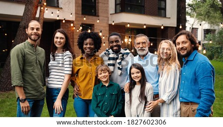 Portrait of mixed-races happy family at dinner outdoor in yard smiling and posing to camera on weekend spending together. Multi ethnic people at barbeque. Celebration. Parents and kids. Generations.