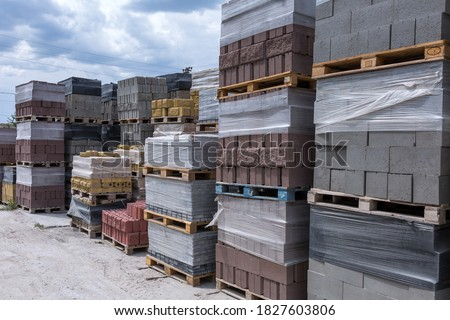 Industrial production of building cement pressed materials. High quality hollow concrete block or cement brick and paving stones. Finished products on pallets packed in film are waiting to be shipped. Royalty-Free Stock Photo #1827603806