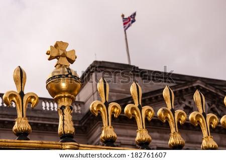 golden fence of buckingham palace with british flag