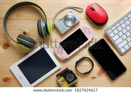 Smartphone with portable game consoles and ebook reader and other electronic gadgets on wooden background.Top view. Royalty-Free Stock Photo #1827624617