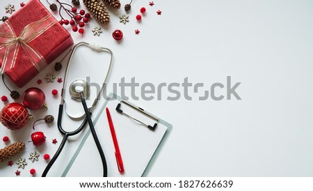 Christmas medical banner gift box,cones, red balls, snowflakes, stethoscope and tablet on white background top view. Copyspace. Medicine new year flatly. Doctor writes down the text. #1827626639