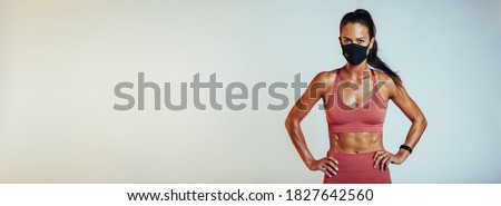 Muscular female wearing sports clothing and face mask with hands on hips against white background. Healthy woman with protective face mask. Royalty-Free Stock Photo #1827642560