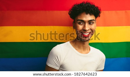 Portrait of a handsome gay man wearing make up against pride flag. Gender fluid male with red lip stick and earring looking away and smiling.
