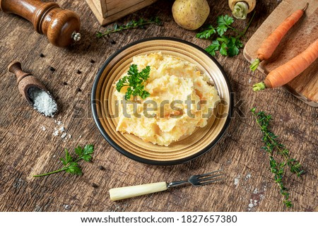 Mashed parsnips with potatoes and carrots and ingredients for making tasty parsnip puree on a dark wooden background. Delicious and healthy vegetarian food rich in vitamins and minerals. Royalty-Free Stock Photo #1827657380