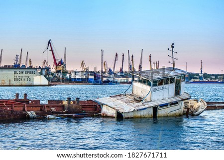 Half drowned boat against the background of a modern seaport. Letters and numbers on the booth are ship number. Shot in Kerch, Crimea