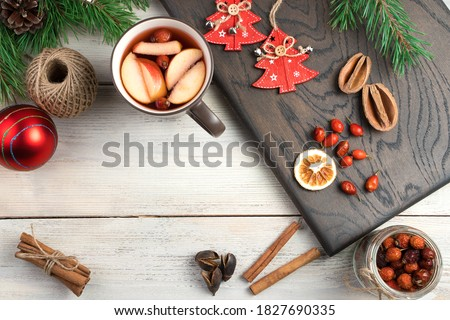 A Cup of mulled wine, berries and dried citrus, cinnamon sticks, fir branches and toys on the Board top view. Holiday background. The concept of New year and Christmas #1827690335