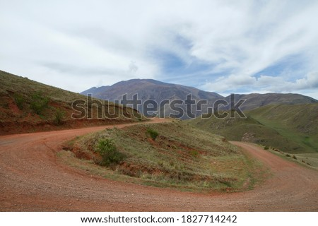 The curved dirt road in the mountains. View of the rural route curve along the hills and green valley.  Royalty-Free Stock Photo #1827714242