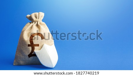 British pound sterling money bag and protection shield. Guaranteed deposits. Strength of financial system. Sustainable banks. Fixed interest deposit. Investment safety. Ease doing business. #1827740219