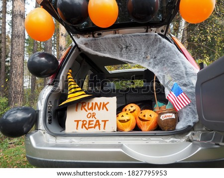 Trick or trunk. Concept celebrating Halloween in trunk of car. New trend celebrating traditional October holiday outdoor. Social distance and safe alternative celebration during coronavirus covid-19 Royalty-Free Stock Photo #1827795953