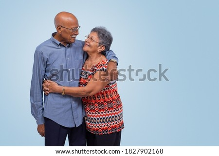 Elderly couple standing, hugging and looking at each other. Light blue gradient background