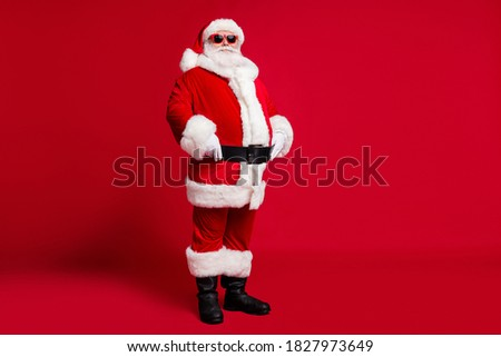 Full length photo of retired old man grey beard hands hips prepare take picture kids wear santa costume gloves coat belt sunglass headwear black boots isolated red color background