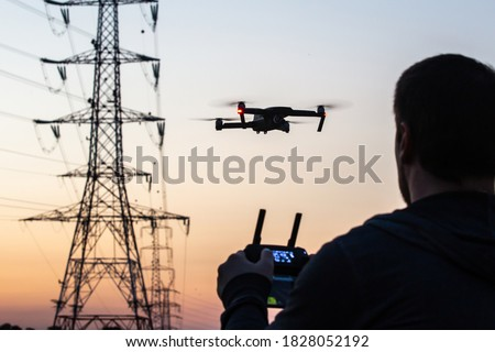 Man operating drone close to the electrical wire/ man holding remote control drones / drone controller. Drone safety. Man operating drone / man holding remote control drones. #1828052192