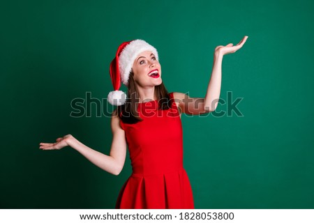 Portrait of her she nice attractive pretty lovely dreamy cheerful cheery girl holding on palms copy space enjoying festive miracle fairy Eve Noel isolated over green color background Royalty-Free Stock Photo #1828053800