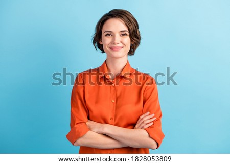 Photo of attractive charming lady cute bobbed hairdo arms crossed self-confident person worker friendly smile good mood wear orange office shirt isolated blue color background Royalty-Free Stock Photo #1828053809
