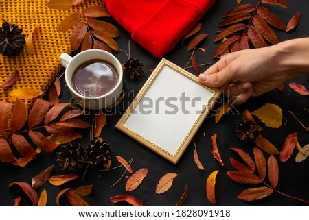 holding an empty photo frame in hand next to a Cup of tea on a black background with autumn leaves, pine cones and needles, scarf and hat for cold weather