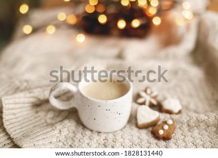 Warm coffee in stylish cup on background of cozy knitted sweater with christmas gingerbread cookies and warm lights. Atmospheric winter hygge. Happy Holidays Royalty-Free Stock Photo #1828131440