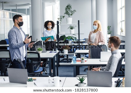 Social distancing in public place, disease prevention during quarantine, staff safety. Meeting and reporting on project or team building by employees and boss in office interior with devices Royalty-Free Stock Photo #1828137800