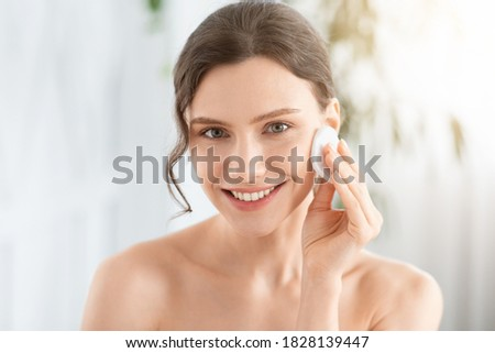 Smiling pretty young woman cleaning her face, using cotton pads and cleansing product, closeup. Young attractive lady using face toner and cotton pad, home interior, empty space, face care products #1828139447