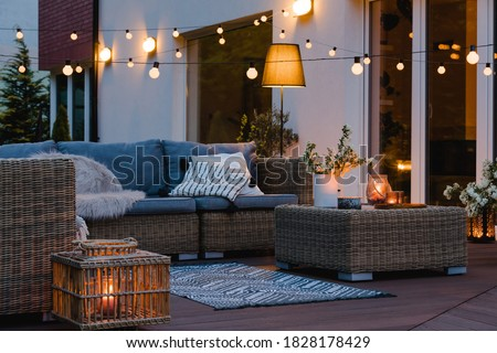 Summer evening on the patio of beautiful suburban house with lights in the garden garden #1828178429