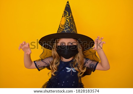 A little cute girl dressed as a Witch on an orange background in a black medical mask plays trick or treat. Child celebrates Halloween at home, in self-isolation in quarantine due to global pandemic Royalty-Free Stock Photo #1828183574
