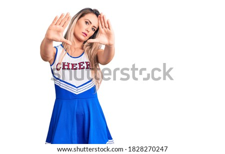 Young beautiful blonde woman wearing cheerleader uniform doing frame using hands palms and fingers, camera perspective