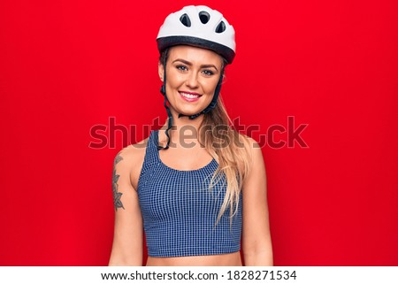 Young beautiful blonde cyclist woman wearing bike security helmet over red background with a happy and cool smile on face. Lucky person.