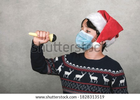 Merry Christmas,kid with medical mask singing Christmas carols with a microphone over gray background