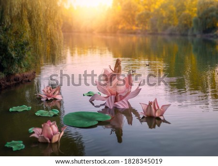 Happy little woman Thumbelina stands in a pink flower lotus. Cute girl in harmony with nature. Fantasy photo. Background is a mystical fairytale autumn lake, green and orange trees, blue water sunset