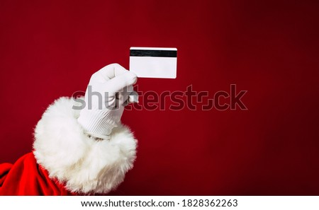 Close up photo of Santa Claus hand in white glove holds bank credit card isolated on a red background