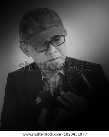 Asian man with glasses, wearing a hat, and a black coat was looking at a DSLR camera he was holding. The black and white portrait concept of a cool professional photographer.