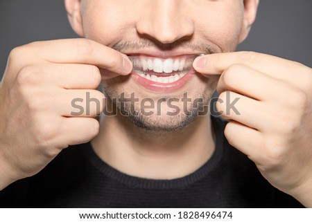 man apply whitening strip on his teeth by hands while smiling into camera  Royalty-Free Stock Photo #1828496474